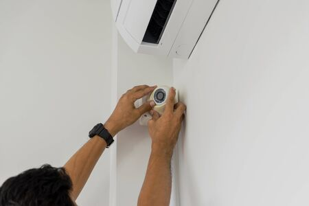Technicians are installing a cctv camera on the roof, can connect to the Internet, and control the camera via a smartphone or tablet.
