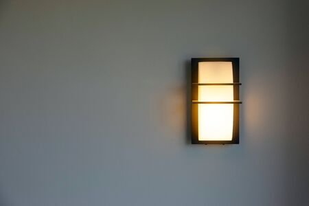 Close-up of a modern design of a wall mounted house lighting on white cement walls.