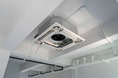 Four-way air conditioner mounted on the ceiling of the room, used for home or office.