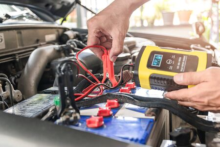 The car mechanic is using a voltage measuring instrument and charging the battery, the cars battery power.
