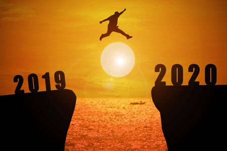 Silhouette of young business mans jumping from the cliff that has the year number 2019 to the side that has the year number 2020 with sun rise at the sea background, Concept for new year target.