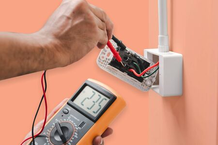 Electrician is using a digital meter to measure the voltage at the power outlet  isolated on orange color pastel background, with clipping path. Imagens