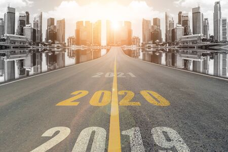 The number 2020 symbol represents the new year on the road heading to the city with beautiful skyscrapers background, New Years and business target concepts.