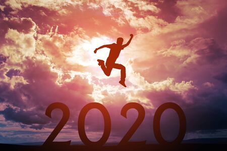 Silhouette of young man jumping over the numbers 2020 years with beautiful sunset, concepts of news year and business target.