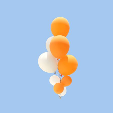 Group of orange and white color balloons for decoration in celebrations of various important days isolated on blue background, with clipping path.
