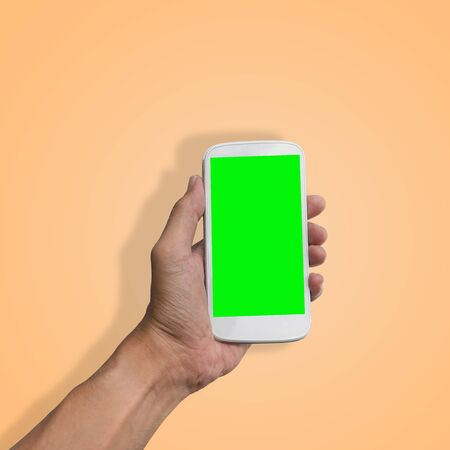 Hand holding smart-phone with green screen isolated on beautiful pastel color background, with clipping path.