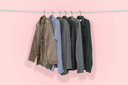 Mens suits and jackets hung on clothes hangers isolated on pink pastel color background, with clipping path.