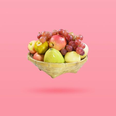 Group of many fruits in a bamboo basket isolated on beautiful pink color pastel background, with clipping path. Imagens