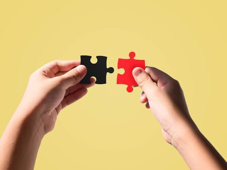 Hands holding black and red color jigsaws isolated on beautiful pastel color background.