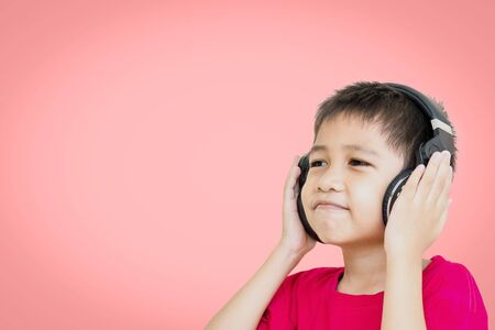 Asian boy wearing a red shirt and wear wireless headphones to listen to music and smiling happily isolated on beautiful pastel color background.