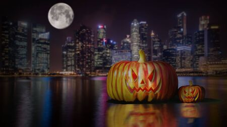 Halloween pumpkins at night under the full moon with the city night background.