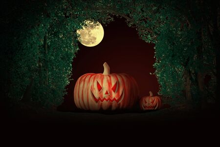 Halloween pumpkins at night under the full moon in the forest.