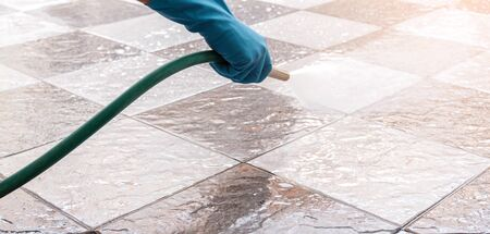 Hand of man wearing blue rubber gloves using a hose to cleaning the tile floor. Foto de archivo - 134469746