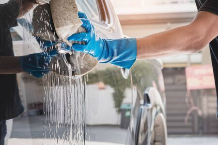 Car wash staff wearing blue rubber gloves using a sponge moistened with soap and water to clean the car. Reklamní fotografie