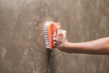 Mens hands are used to convert polishing cleaning on the concrete wall. Reklamní fotografie