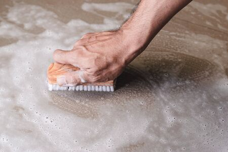Mens hands are used to convert polishing cleaning on the tile floor.