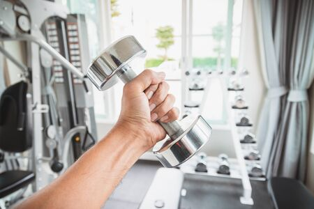 Closeup a mens hand holing a dumbbell with his left hand in the gym, Concept for exercise and health care.