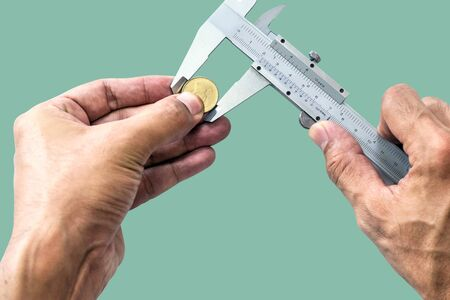 Closeup a man's hand is using Vernier to measure the size of a coin isolated on pastel color background. Archivio Fotografico