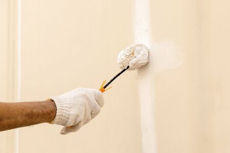 Closeup on hand wearing white cloth gloves, using a roller for painting white color on the concrete wall. Standard-Bild