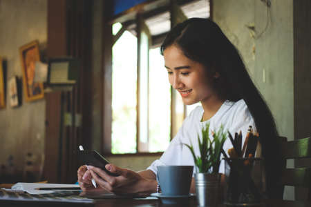 Portrait of happy young woman working on tablet pc while sitting at her working place in office. Imagens