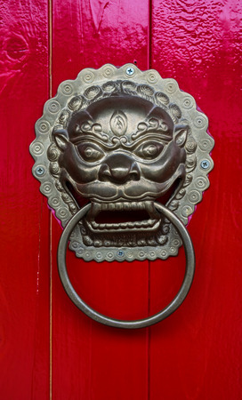 tradional: Head gold lion knock on the red wooden door. Stock Photo