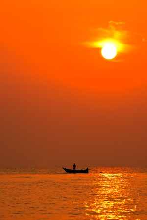 Silhouette fisherman and boat on horizon photo