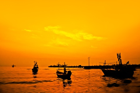 silhouette of fishing boat with yellow and orange sun in the background photo