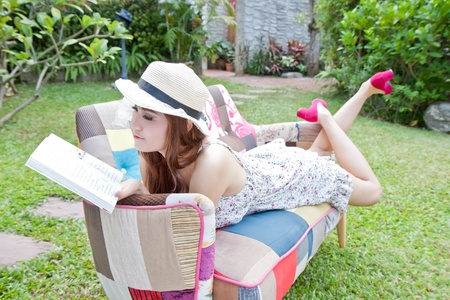 briskness: Beautiful asian woman reading her book in the garden
