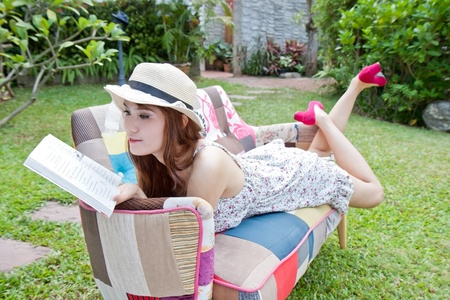 Beautiful asian woman reading her book in the garden