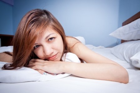 Beautiful young Asian woman relaxing on the bed Stock Photo - 13793691