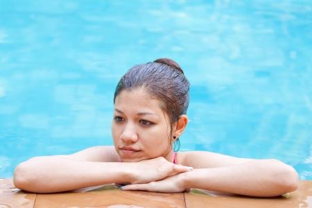 Beautiful Asian woman relaxing in the swimming pool photo