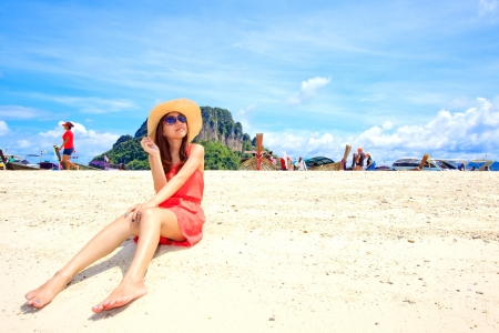 Asian woman in a pink dress relaxing on the beach