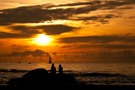 Silhouette sunrise of woman sitting on stone near by the sea photo