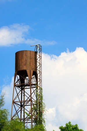 Old water tank tower on blue sky