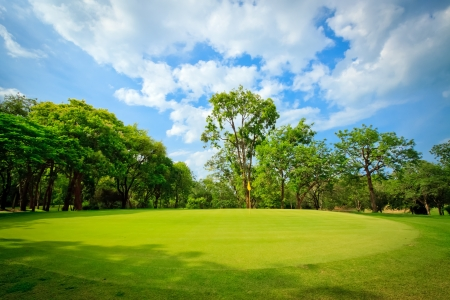green golf field with cloudy sky Stock Photo