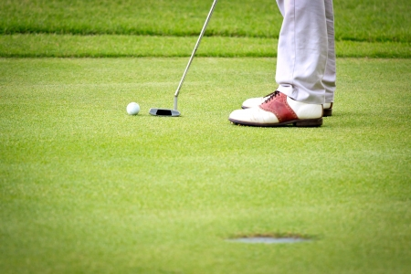 Feet of male golf player putting at green photo