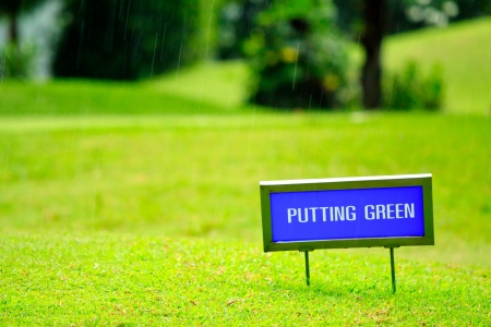 Putting green guidance board in the foreground and golf players Stock Photo - 14042966