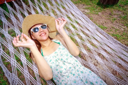 Asian woman relaxing on the beds beside garden photo