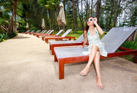 Asian woman relaxing on sun beds beside garden photo