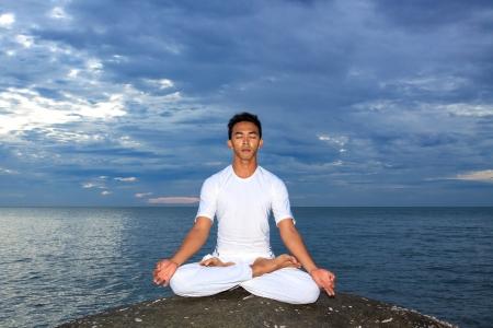 Asian male model: Chân dung người đàn ông trẻ châu Á làm bài tập yoga trên đá với mây trời và đại dương, Thái Lan Kho ảnh
