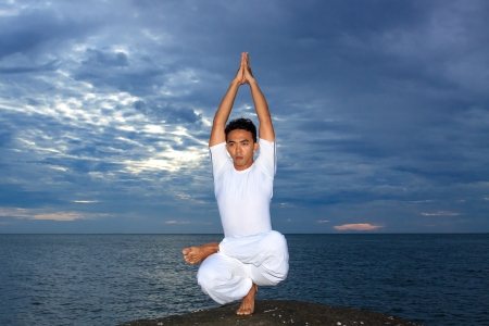 Portrait of Asian young man doing yoga exercise on stone with cloudy sky and ocean, Thailand Stock Photo - 14244788