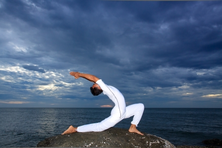Portrait of Asian young man doing yoga exercise on stone with cloudy sky and ocean, Thailand photo