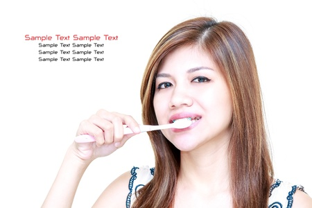 Young Asian Woman smiling and brushing her teeth on white background photo