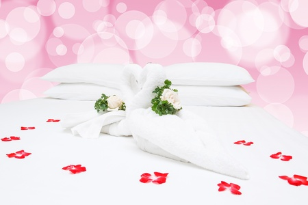 Close up of two nice towels swans on white bed sheet photo