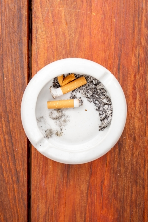 repugnant: Smoked cigarettes in white ashtray on wood table