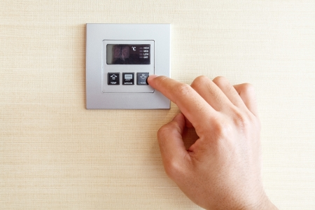 Hand with finger on air conditioner switch control