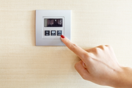 Womans hand with finger on air conditioner switch control photo