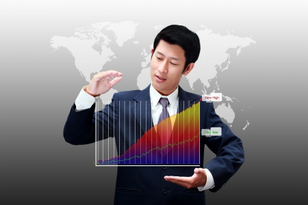 Business man holding a chart of business growth with new high photo