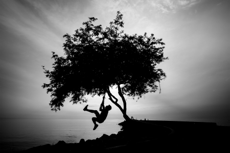 Silhourtte of Lonely man hanging his body under the tree Stock Photo