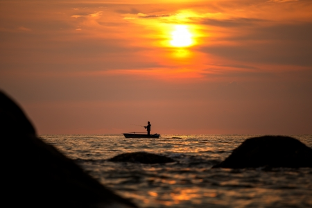 Fisherman silhouette on sunrise, Thailand photo